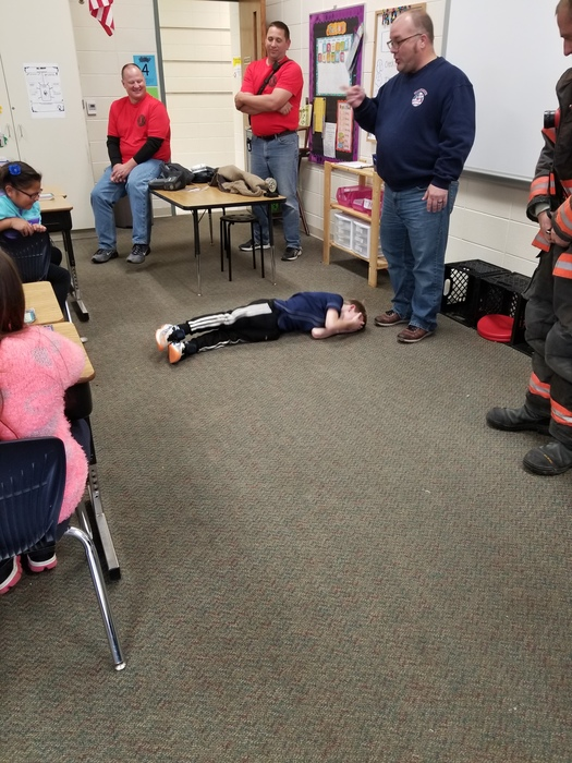 The firefighters are teaching students to stop, drop, and roll.